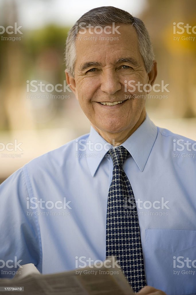 Senior man wearing suit and tie holding newspaper royalty-free stock photo