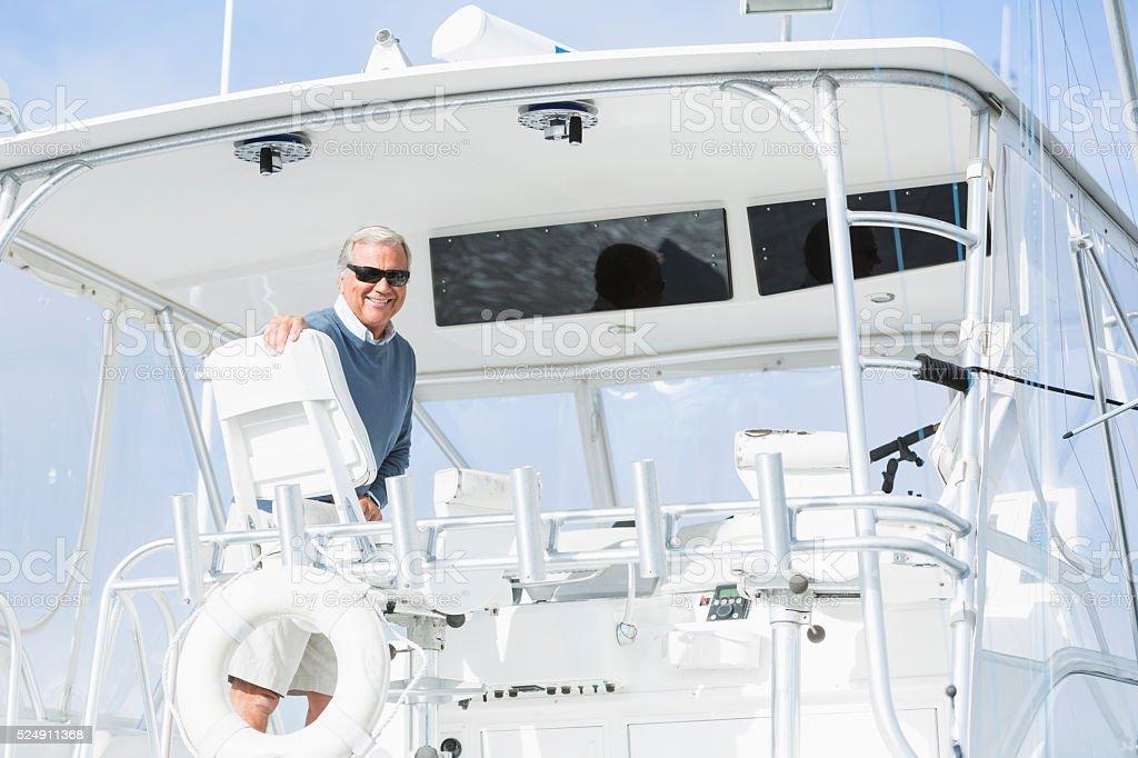 Senior man wearing sunglasses on his boat stock photo