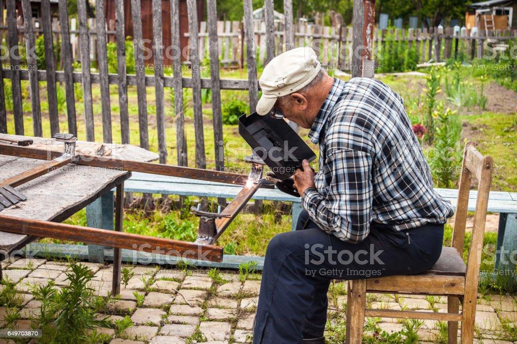 Senior man welding metal structure stock photo