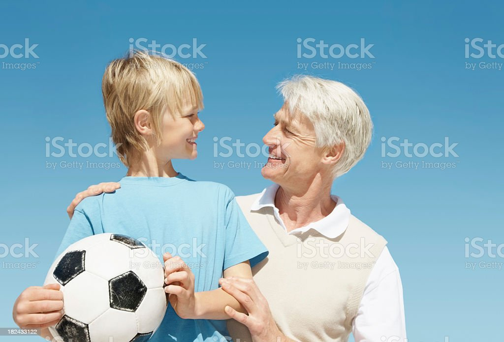 Senior man with a boy holding football against sky royalty-free stock photo