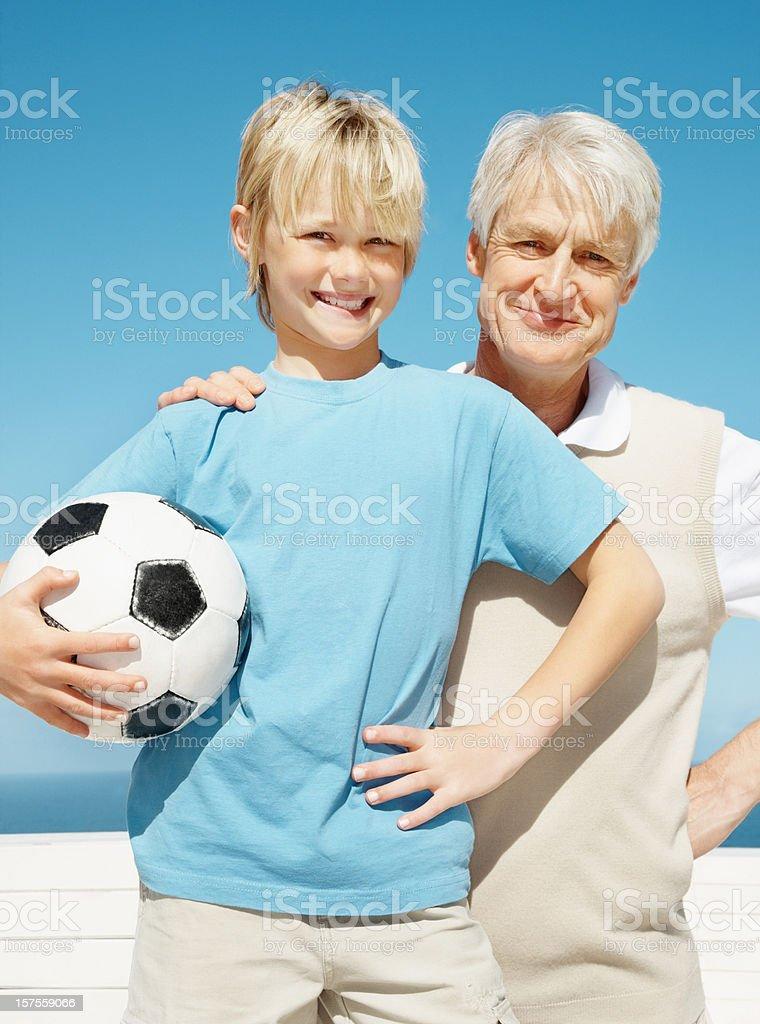 Senior man with a boy holding football royalty-free stock photo