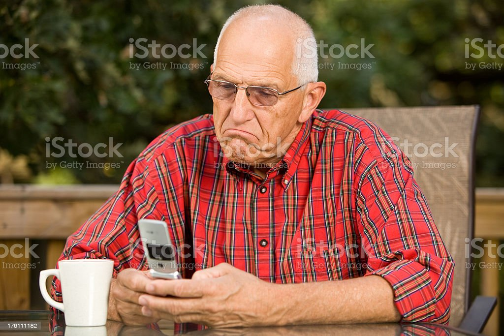 Senior Man with a Frown Texting on his Mobile Phone royalty-free stock photo