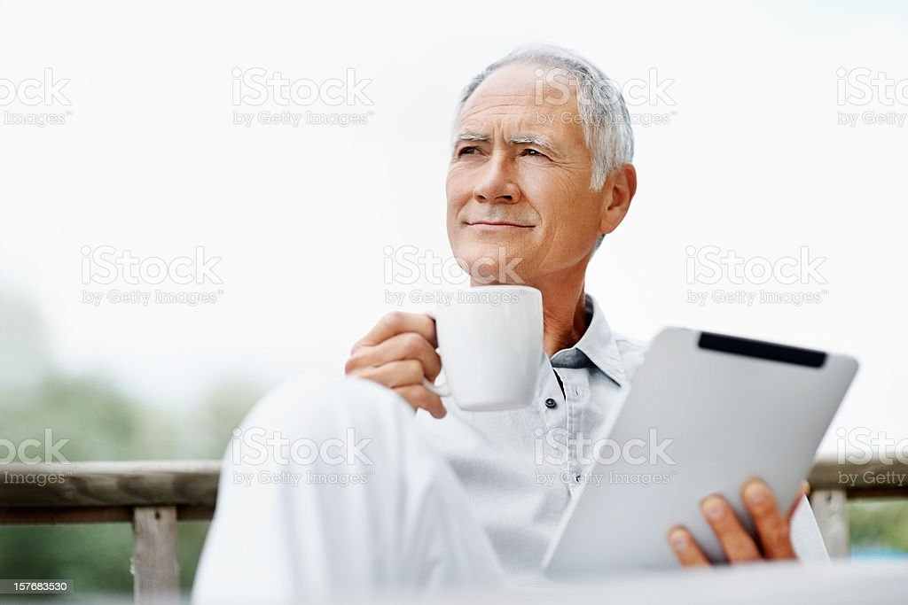 Senior man with a tablet PC holding coffee mug royalty-free stock photo