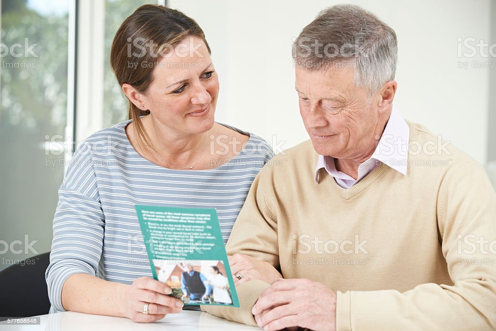 Senior Man With Adult Daughter Looking At Brochure For Retiremen stock photo