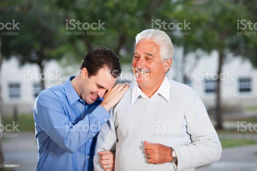 Senior man with adult son laughing stock photo
