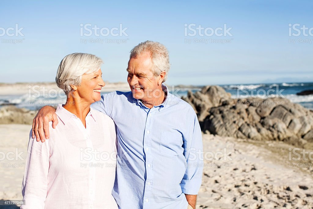 Senior Man With Arm Around Woman Walking On Beach royalty-free stock photo