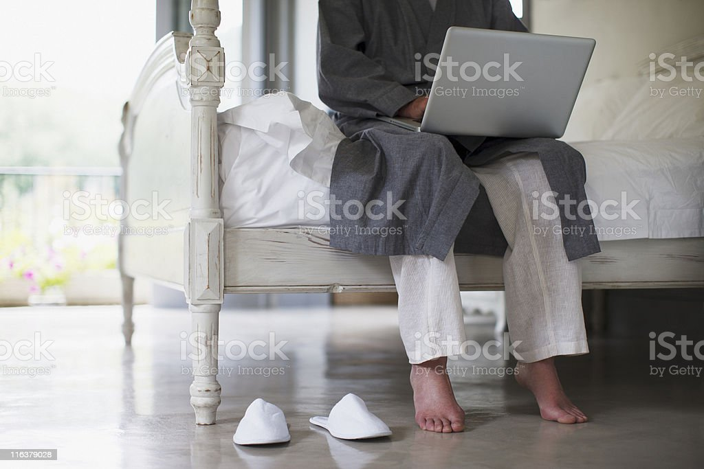 Senior man with bare feet sitting on edge of bed using laptop royalty-free stock photo