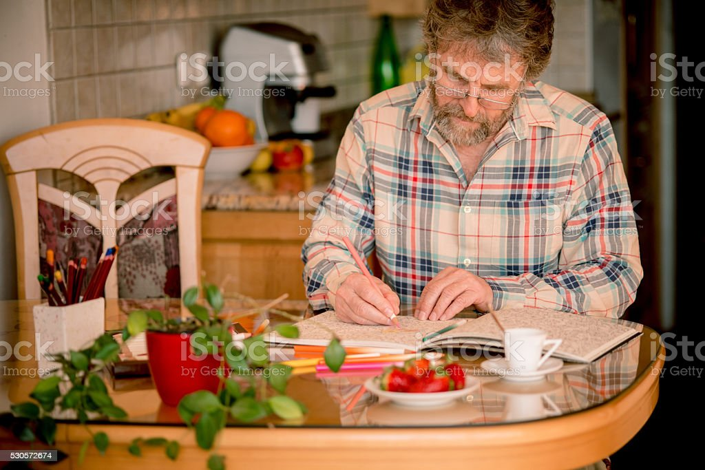 Senior Man with Beard Coloring Book and Having Coffee,  Europe stock photo