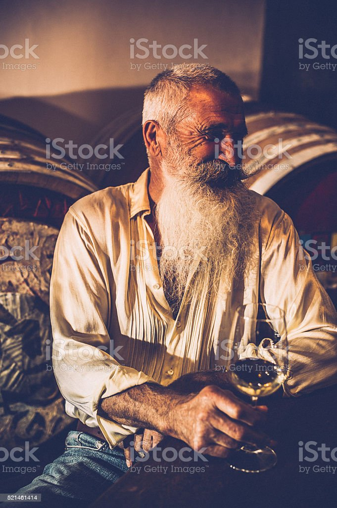 Senior Man with Beard Holding Glass of Wine in Winecellar stock photo