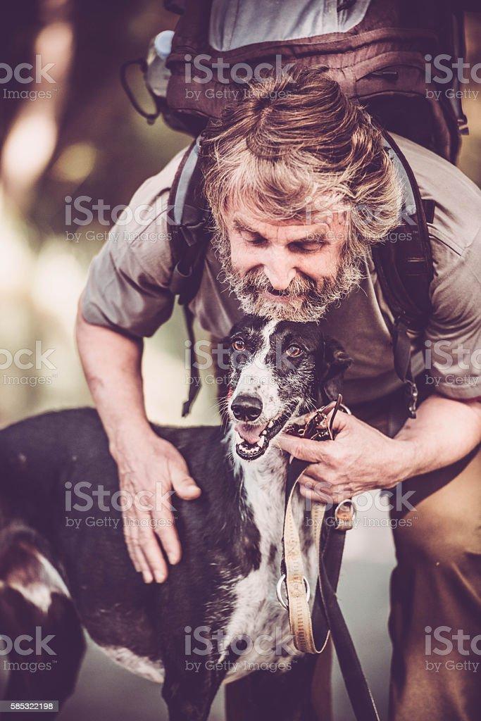 Senior man with beard - Mountaineer and his greyhound dog stock photo