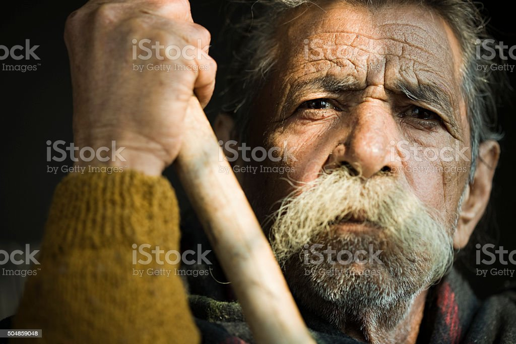 Senior man with big mustache, blank expression looking at camera. stock photo