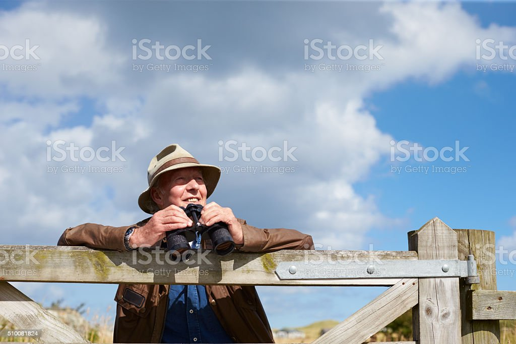 Senior Man With Binoculars Leaning Against Wooden Gate stock photo