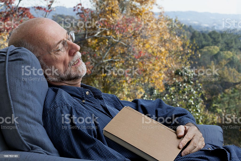 Senior Man With Book Asleep in Chair stock photo