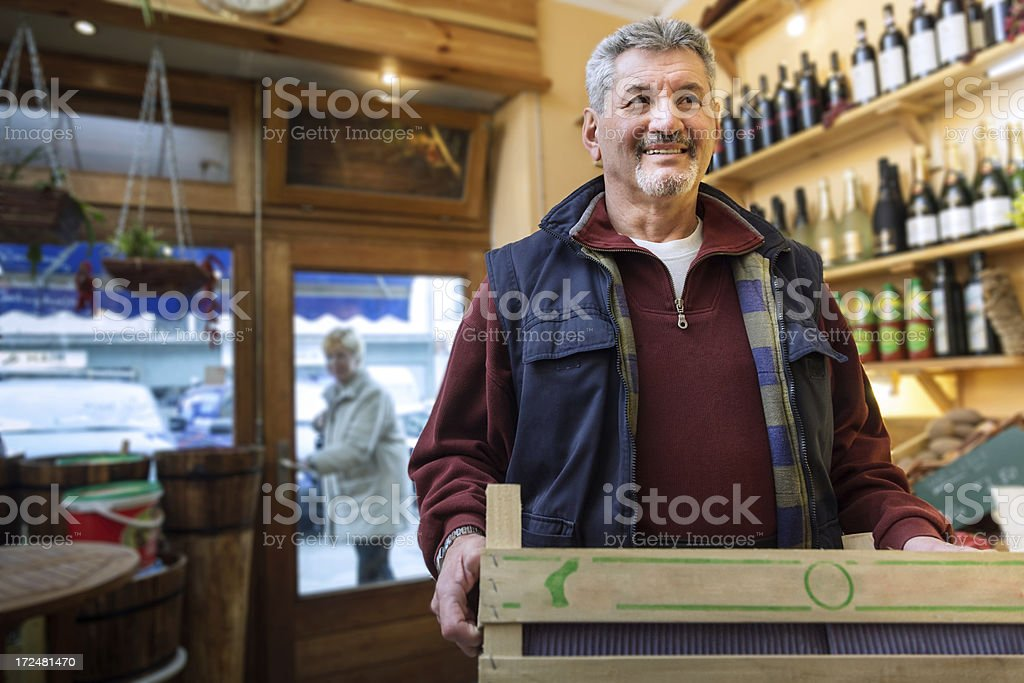 Senior man with box in hands standing inside store stock photo