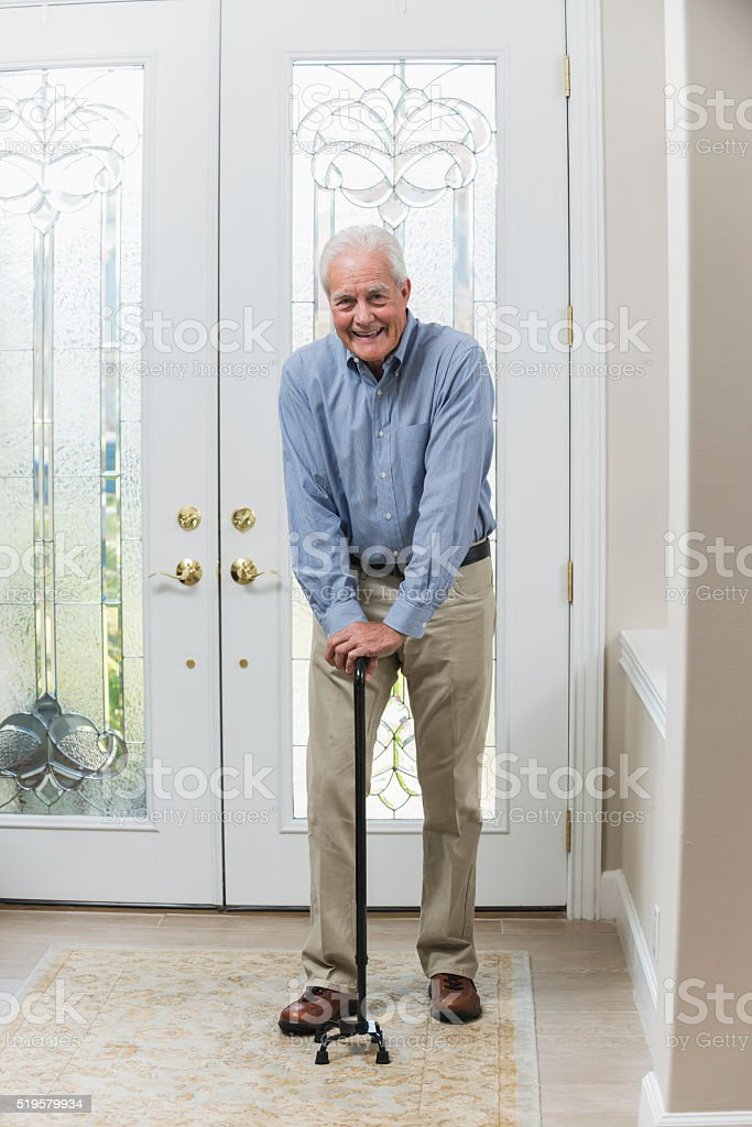 Senior man with cane coming home stock photo