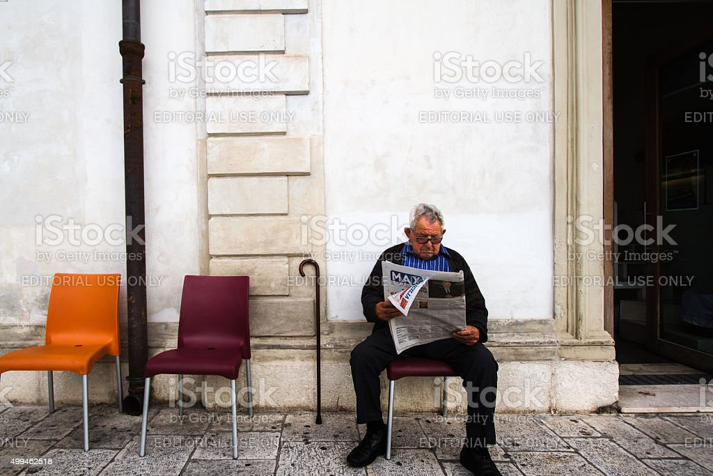 Senior Man with Cane Reading Newspaper Outside Coffee Bar, Sicily stock photo
