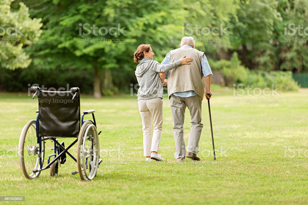 Senior man with caregiver at the park stock photo