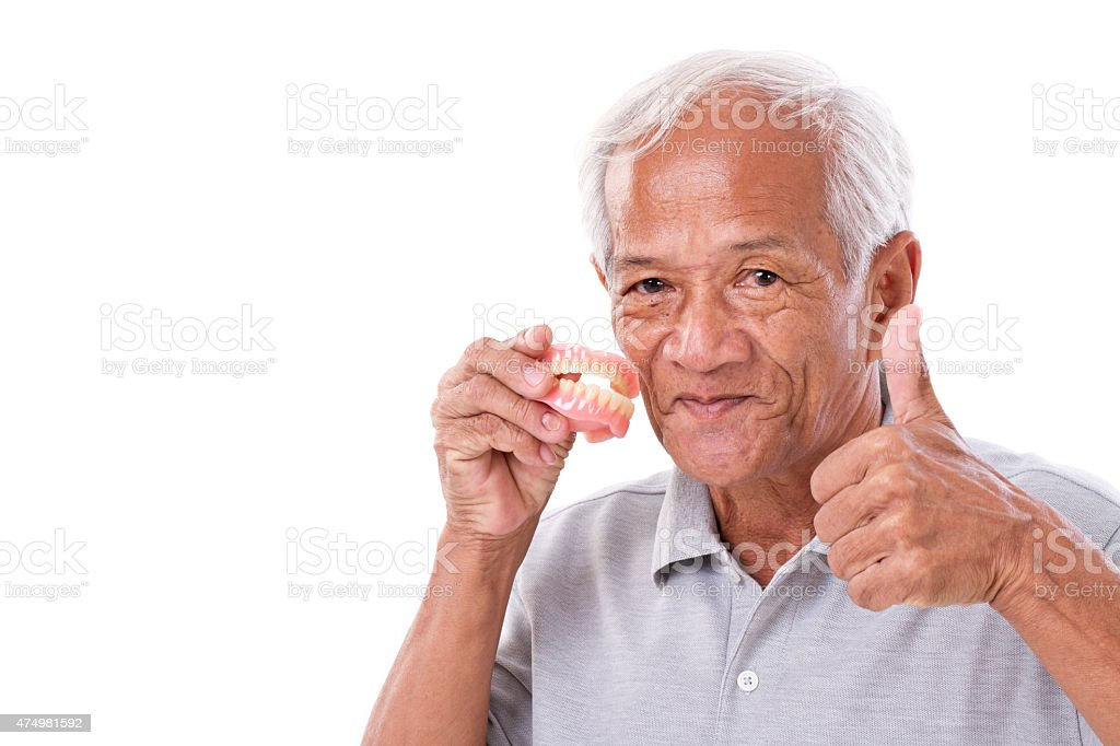 senior man with denture, giving thumb up stock photo