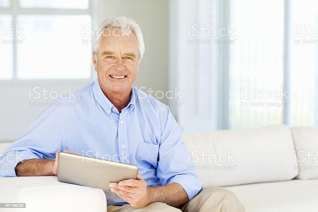Senior Man With Digital Tablet Smiling At Home royalty-free stock photo