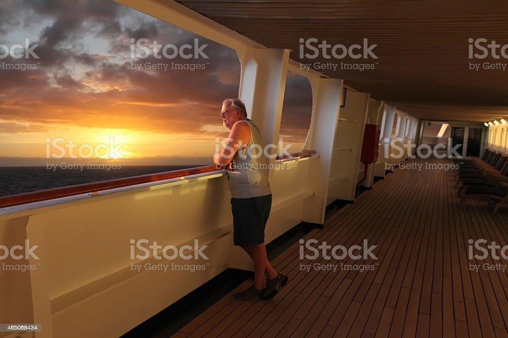 Senior man with eyeglasses at ship rail watching sunset. stock photo