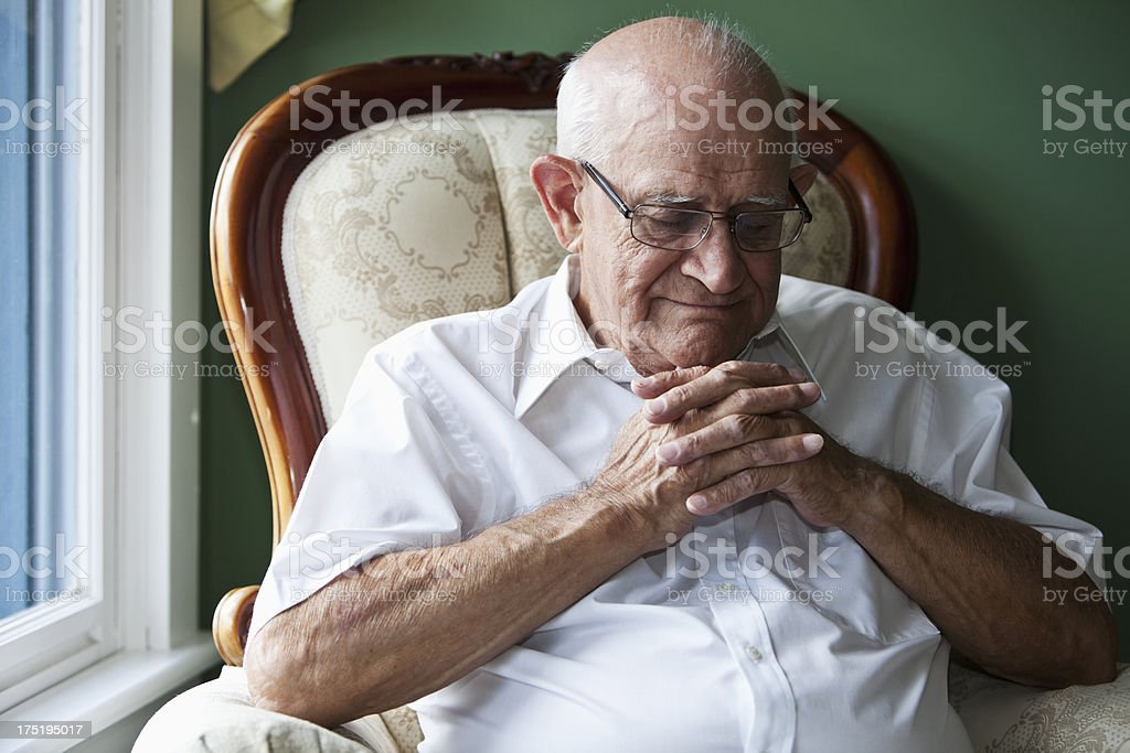 Senior man with eyes closed and hands clasped royalty-free stock photo