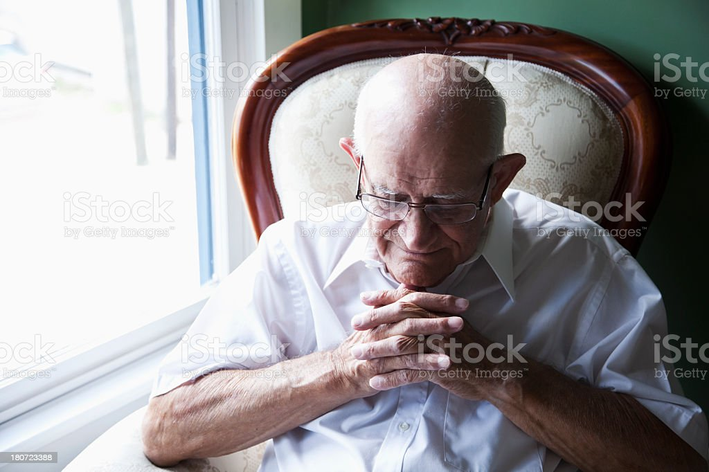 Senior man with eyes closed and hands clasped stock photo
