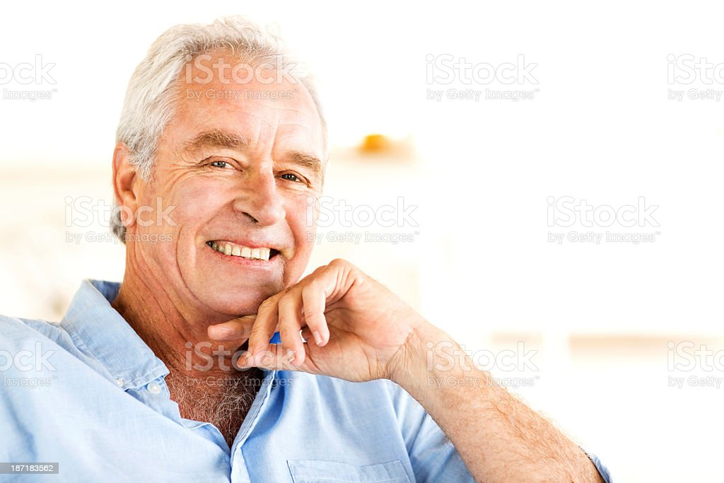 Senior Man With Hand On Chin Smiling At Home royalty-free stock photo