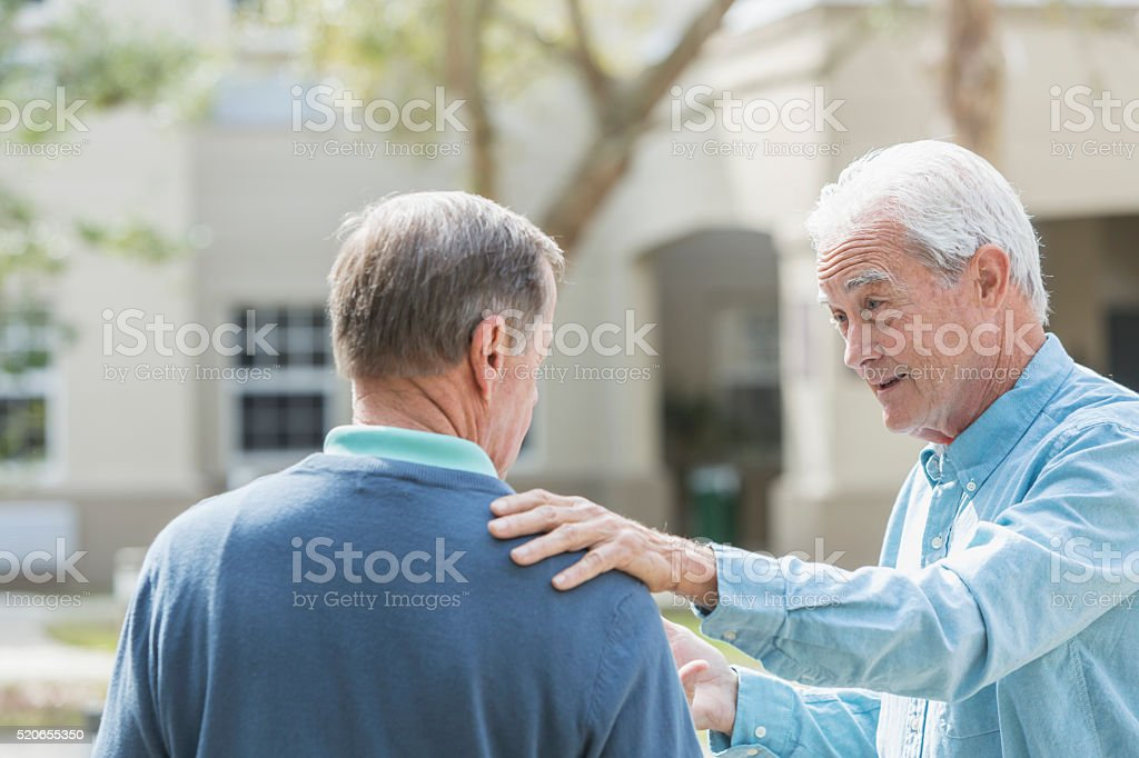 Senior man with hand on his friend's shoulder stock photo