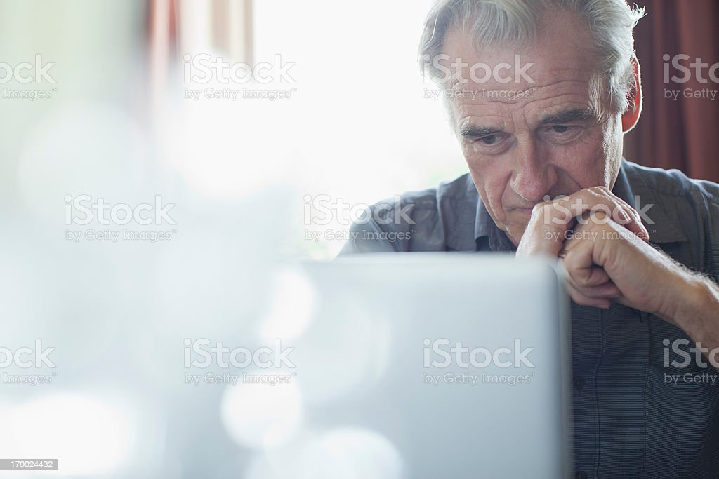 Senior man with hands clasped using laptop stock photo