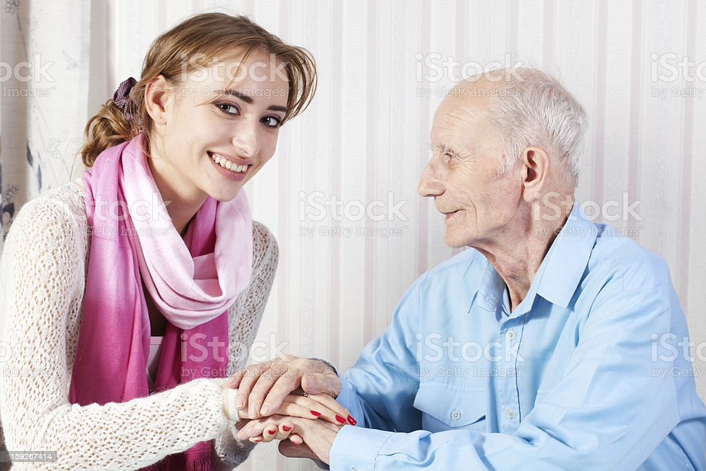 Senior man with her caregiver at home royalty-free stock photo