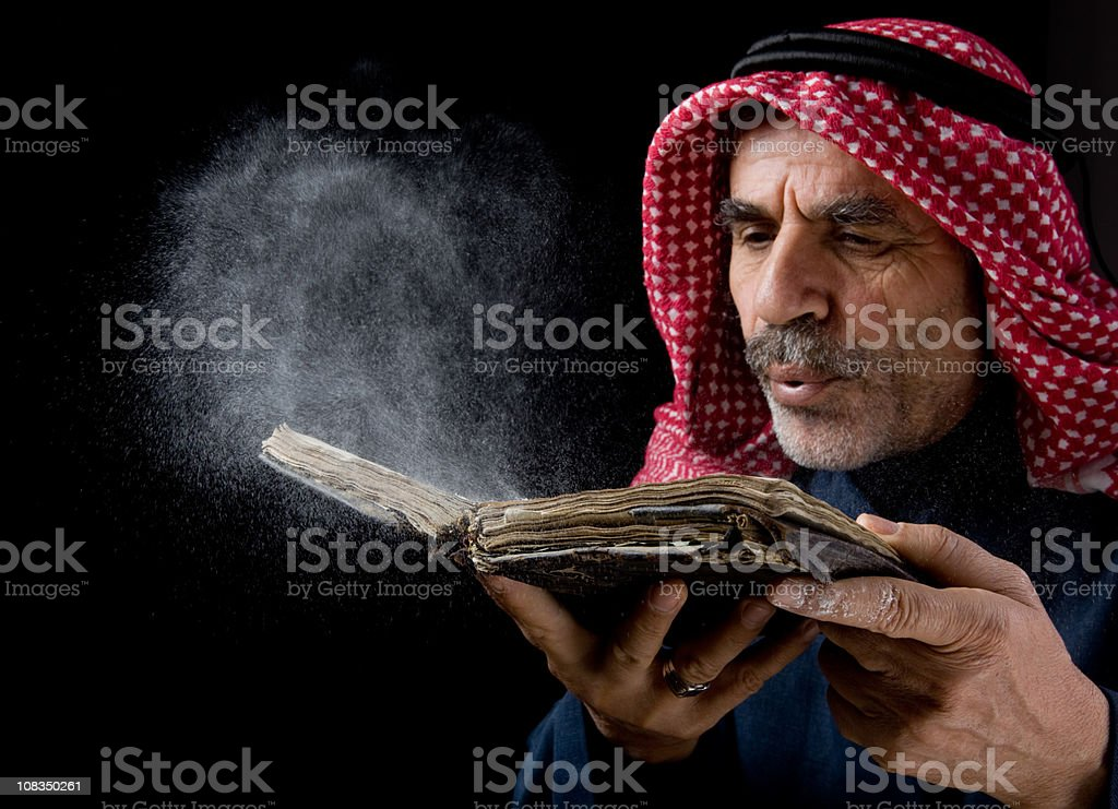 Senior man with kaffiyeh blowing dust over old antique book royalty-free stock photo