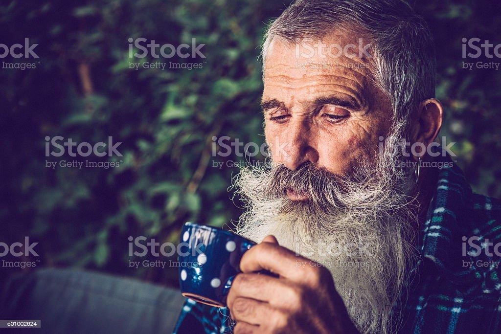 Senior Man with Long Beard Drinking Coffee Outdoors stock photo
