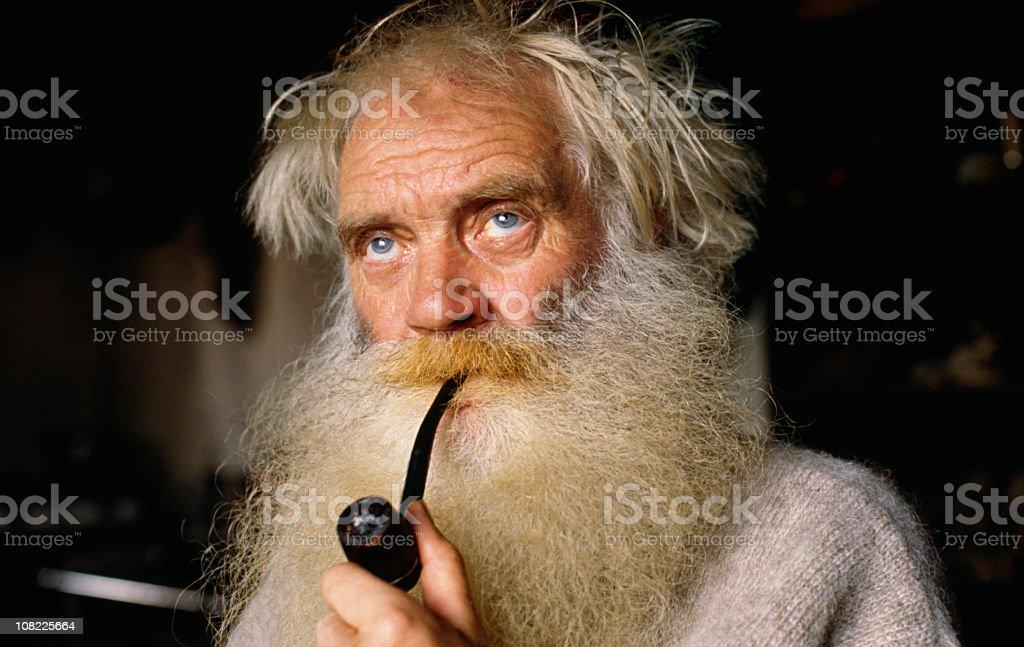 Senior Man With Long Beard Smoking Pipe stock photo