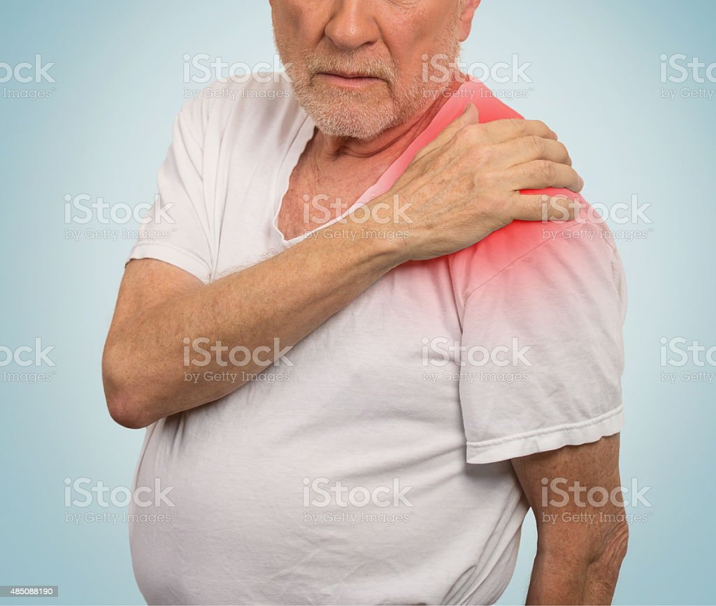 senior man with pain in his shoulder isolated blue background . stock photo