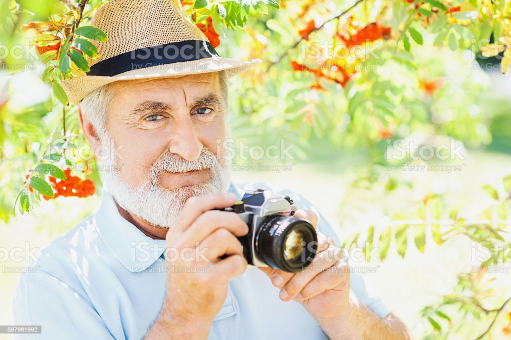 Senior man with photo camera taking pictures stock photo