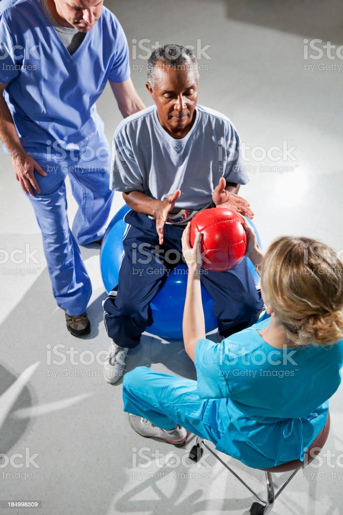 Senior man with physical therapists using fitness balls royalty-free stock photo