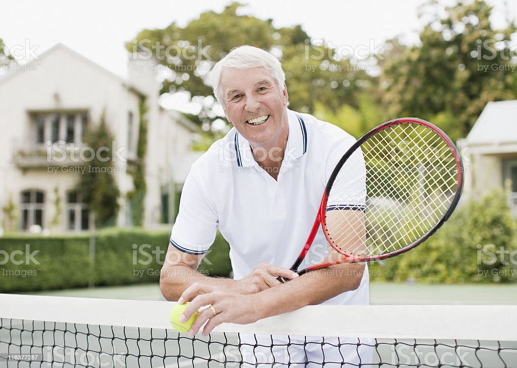 Senior man with racket and ball on tennis court royalty-free stock photo