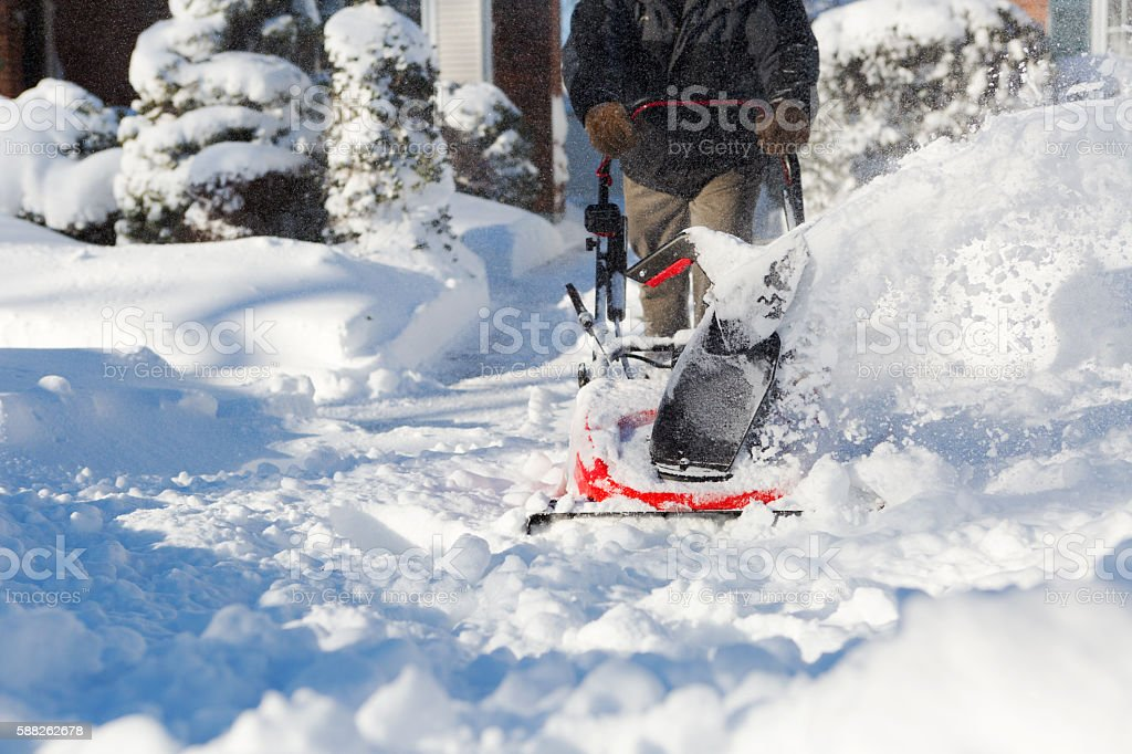Senior man with Snow blower clearing snow stock photo