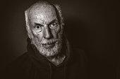 Senior Man with Startled Expression Against Black Background, B&W Image