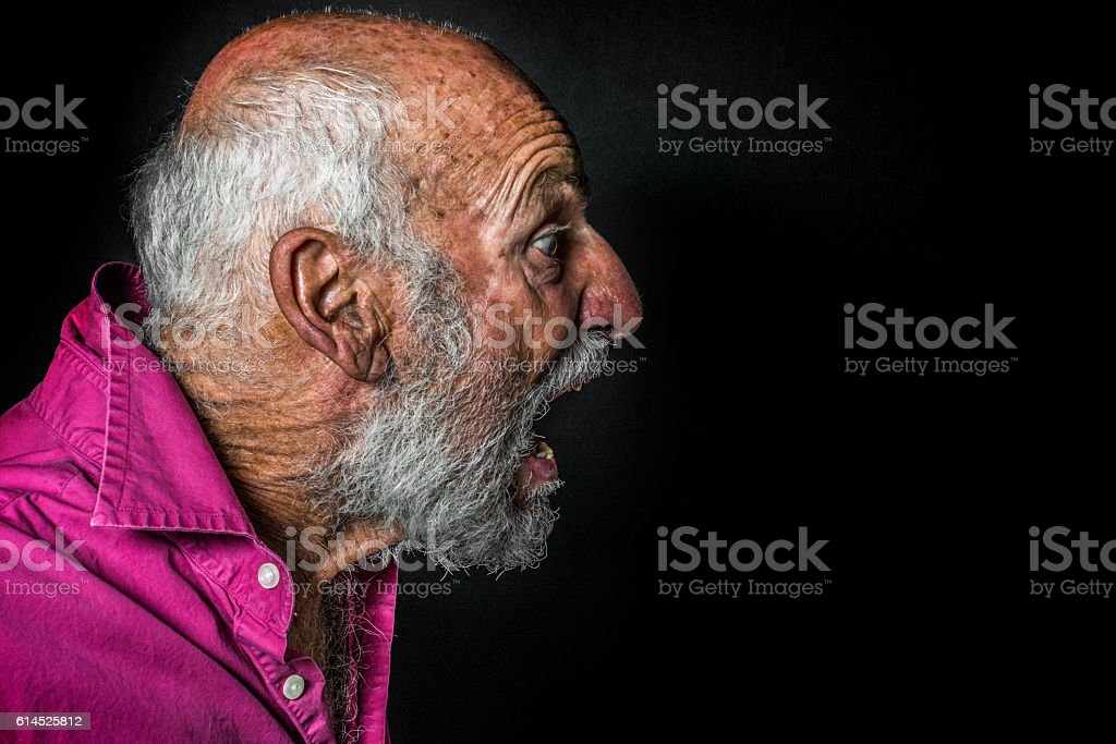 Senior Man with Startled Expression Against Black Background, Low Key stock photo