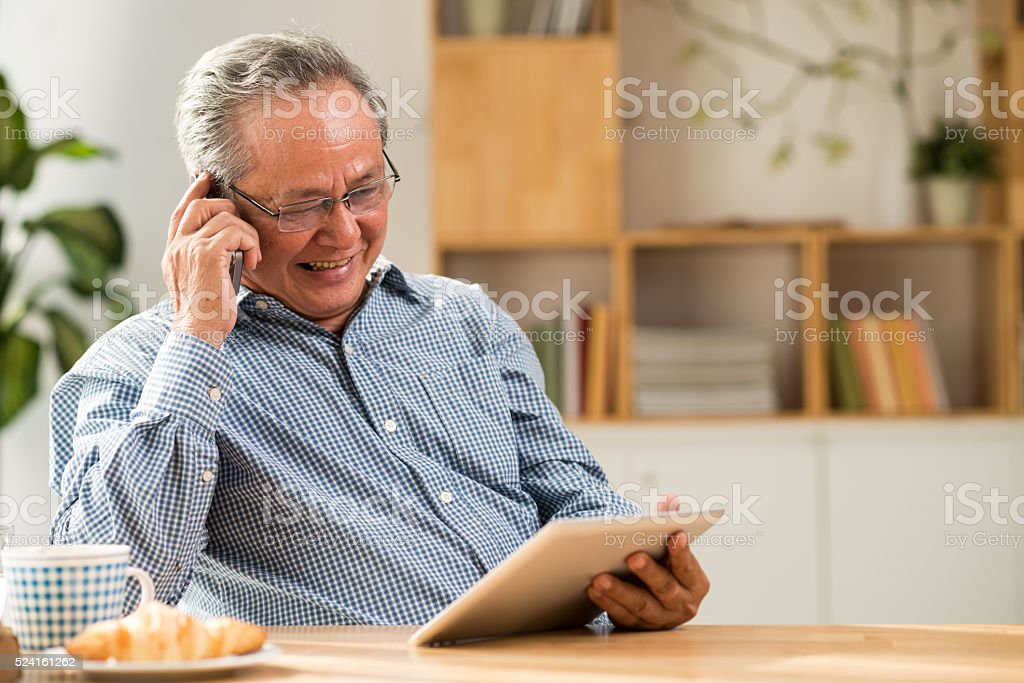 Senior man with tablet and smartphone stock photo