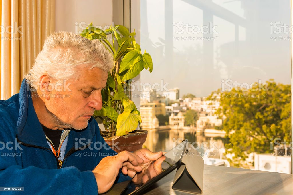 Senior man with tablet at the Lake Pichola stock photo