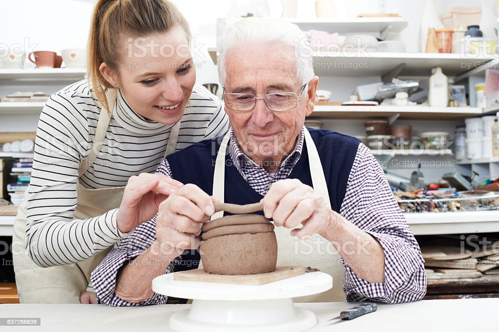 Senior Man With Teacher In Pottery Class stock photo