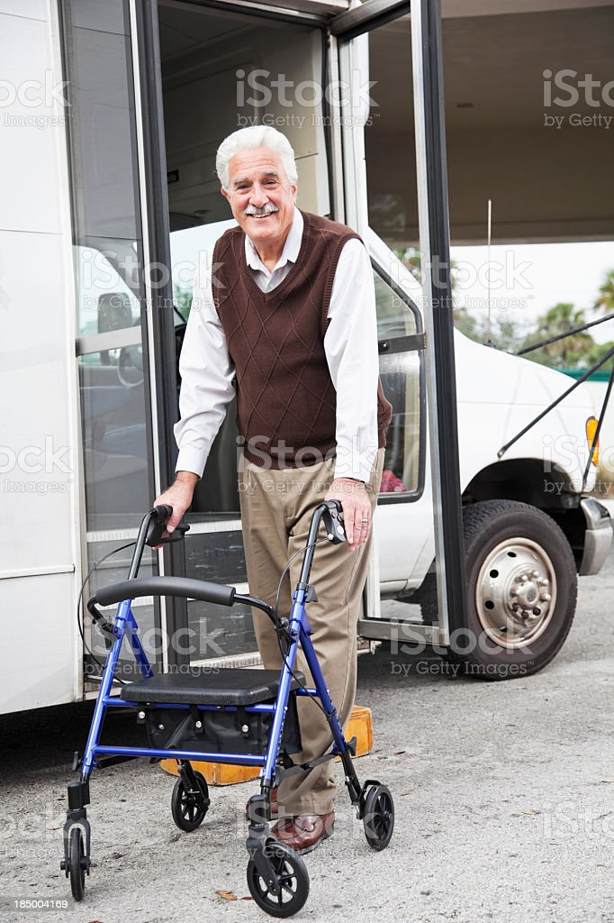 Senior man with walker exiting shuttle bus royalty-free stock photo