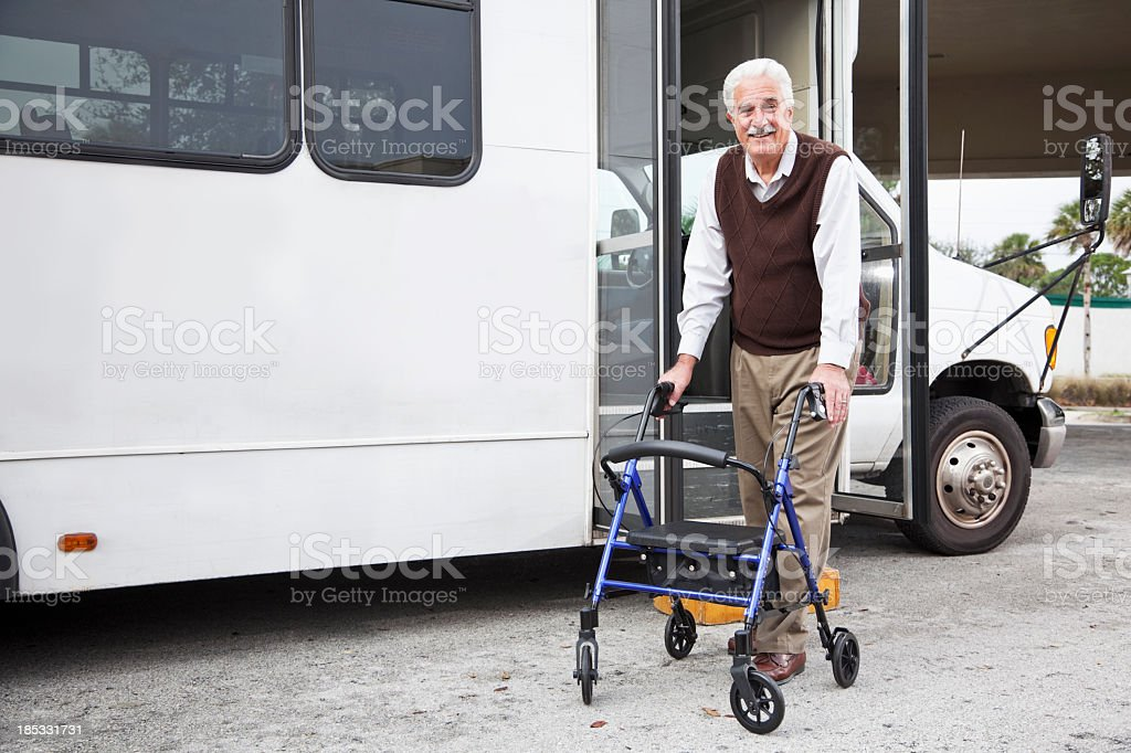 Senior man with walker exiting shuttle bus stock photo