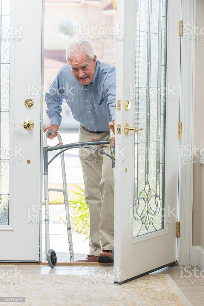 Senior man with walking coming home thru front door stock photo