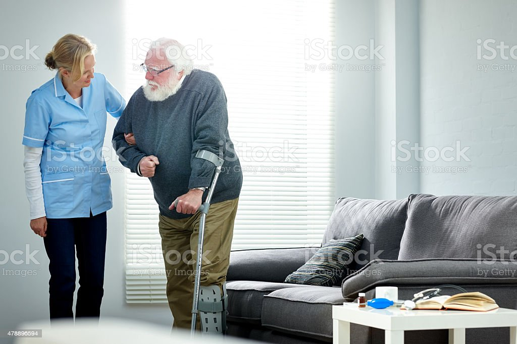Senior man with walking stick being helped by female nurse stock photo