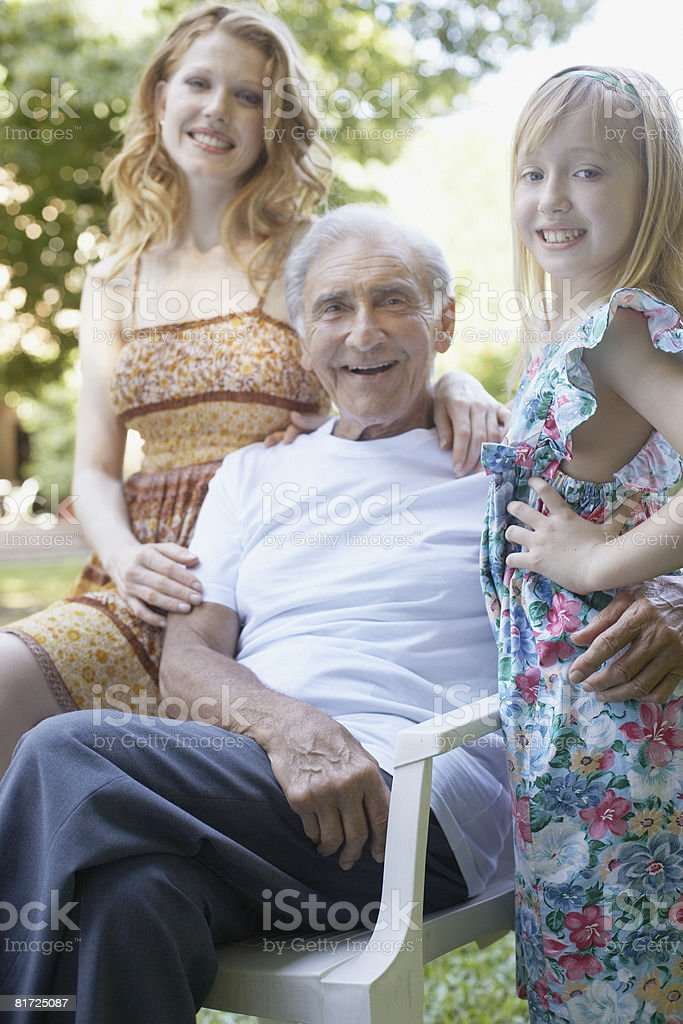 Senior man with woman and young girl outdoors smiling royalty-free stock photo