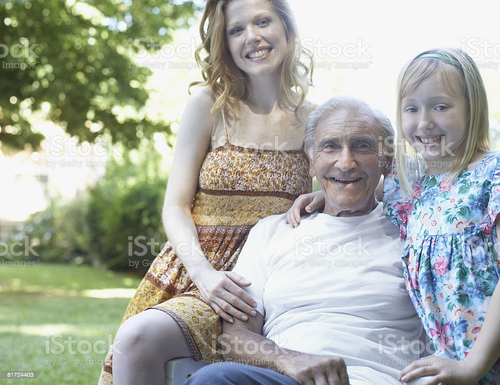 Senior man with woman and young girl sitting outdoors smiling royalty-free stock photo