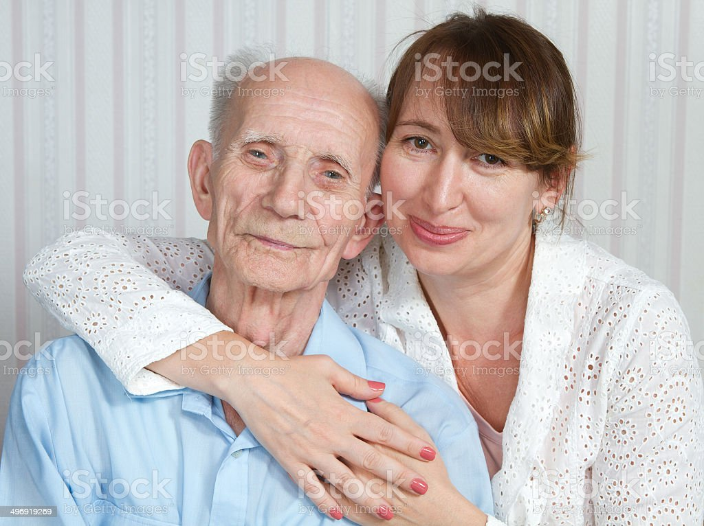 Senior man, woman with their caregiver at home. stock photo
